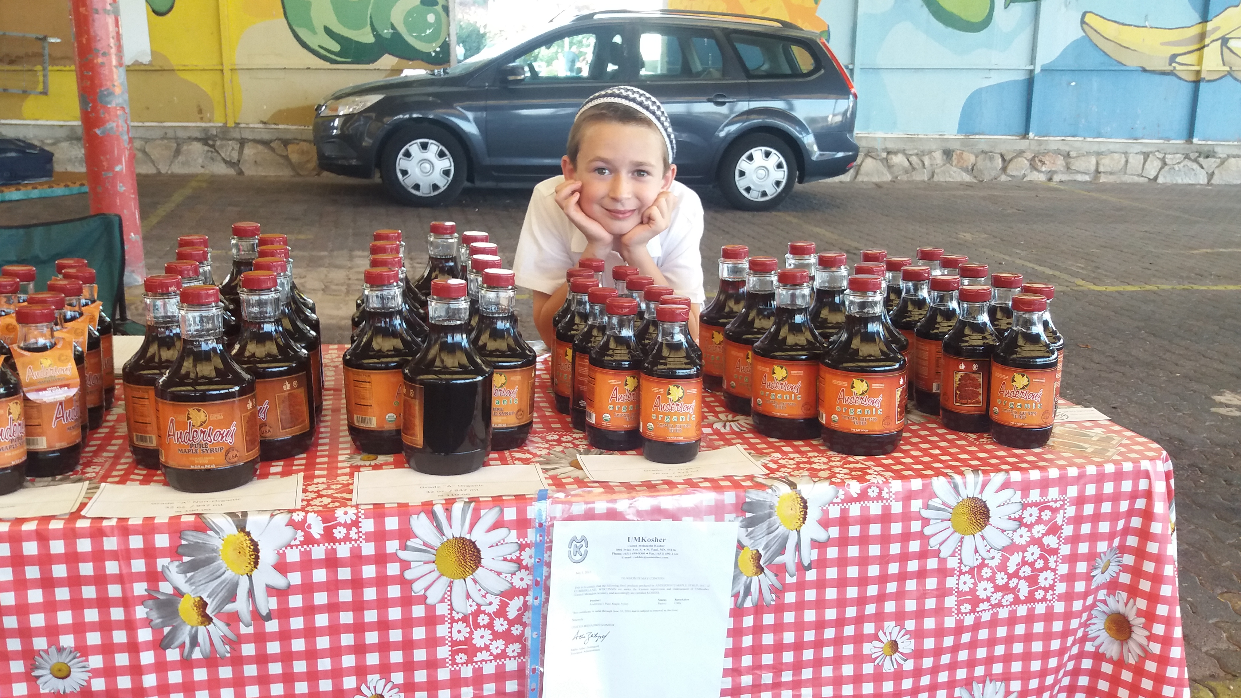 A young boy manning a table loaded with maple syrup at the Karmiel Farmer's Market in Israel