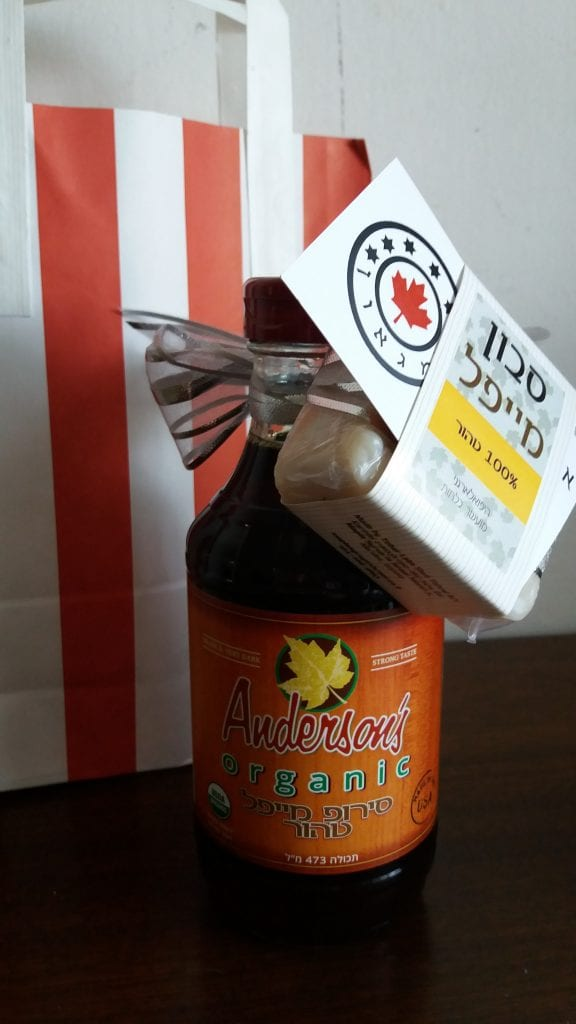 Grade B Organic maple syrup bottle with a bar of vegan maple soap tied up with a ribbon in front of a red and white striped gift bag in Israel